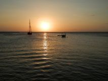 Sunset over the ocean, sailboat and fishing boat. Moored offshore. Tropical island vacation royalty free stock image