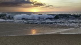 Sunset over the ocean from the shore of Nazaré beach, Playa do Norte, Portugal. The waves break on the shore reflecting the. Colours of the sky on the wet royalty free stock images