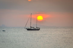 Sunset over ocean with small boat silhouette Stock Photos