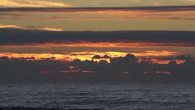 Sunset over the ocean with small waves,clouds and beautiful red sunlight and reflections on the water surface. Sunset over the ocean in Spain with small waves stock video footage