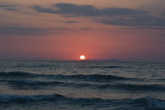 Sunset over the ocean. Sun setting over the sea Royalty Free Stock Image