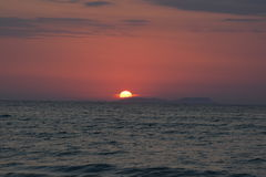 Sunset over the ocean. Sun setting over the sea Royalty Free Stock Photo