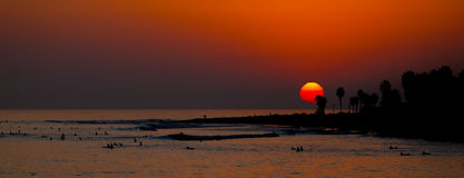 Sunset over the Ocean with surfers Stock Image