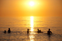Sunset over ocean swimmers Royalty Free Stock Image
