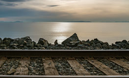 Sunset over the ocean with train tracks and rocks in the foreground. Stock Image