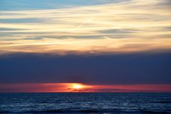Sunset over the Ocean - View of the red sun sinking into the horizon and waves washing over the sand of the beach. Sunset - View of the red sun sinking into the royalty free stock image