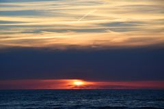 Sunset over the Ocean - View of the red sun sinking into the horizon and waves washing over the sand of the beach. Sunset - View of the red sun sinking into the stock images