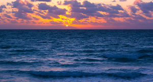 Sunset over the ocean with violet clouds. Stock Photo