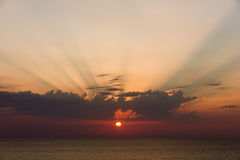 Sunset over the ocean with visible sunshine on the clouds Royalty Free Stock Image