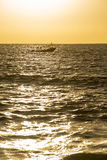 Sunset over ocean water with boat in the horizon Royalty Free Stock Photos