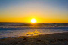Sunset over the ocean with waves. Golden sunset over ocean with waves rolling in splashing on the sandy beach Stock Photo