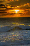 Sunset over the ocean with waves vertical. Orange sunset over ocean with waves rolling in splashing on the sandy beach Stock Photography