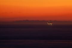 Sunset over oil rig in sea Stock Photography