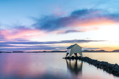 Sunset over old boat house. Blue, purple and yellow sunset over a quiet sea and old boathouse in horizon Stock Photography