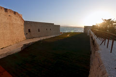 Sunset over old castle. Sunset over battlements of old castle with sea in background Royalty Free Stock Photos
