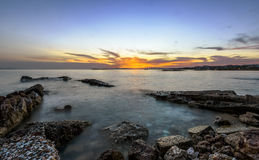 Sunset over old pier in the sea in south Athens Royalty Free Stock Images