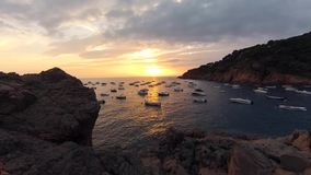 Sunset over one of the bays of the Costa Brava. A sunset through clouds at Costa Brava with bay view stock footage