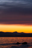 Sunset over pacific ocean. Beautiful sunset with dark mountains and orange and blue, drammatic sky over pacific ocean Stock Image