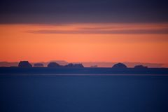 Sunset over pack ice with icebergs, East Greenland. Pack ice, Scoresbysund, East Greenland, wintertime Royalty Free Stock Images