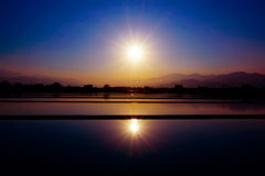 Sunset over a paddy field. Which is full of water stock photo
