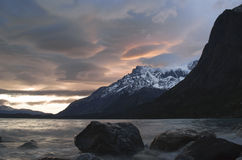 Sunset over a patagonian lake surrounded by snowy mountains Stock Image