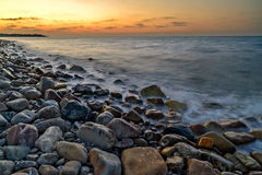Sunset over pebble beach Stock Photo