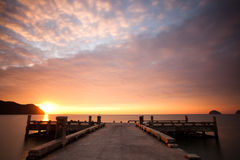 Sunset over pier and sea. Orange sunset and cloudscape over sea with pier in foreground Stock Photos