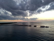 Sunset over the pier. Sun setting over a pier in the Bahamas Royalty Free Stock Photography