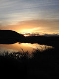 Sunset Over Pond. Sun setting over hills reflecting off pond Stock Photo