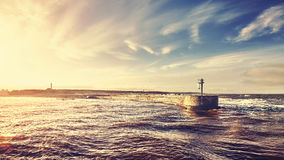 Sunset over port entrance in a storm. Stock Photos