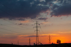 Sunset over power poles, blocks of flats and a tree Royalty Free Stock Photo