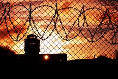 Sunset over prison yard. Sun setting over prison yard; sky is orange and yellow Royalty Free Stock Photo