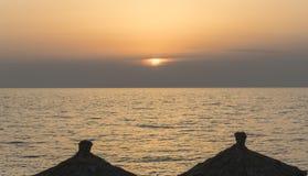 Sunset over reed sun umbrellas and sea on the sandy beach Stock Photos