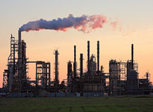 Sunset over the Refinery. Sunset captured behind an oil refinery with smoke billowing into the sky stock image