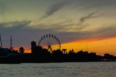 Sunset at Tigre with ferris wheel. Sunset over Rio Tigre with the silhouette of a big ferris wheel Royalty Free Stock Images