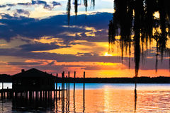 Sunset over river. Sunset over a river of glistenting water with a dock and boathouse and spanish moss in the foreground Stock Image