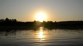 Sunset over the river, boat sails along the river stock footage
