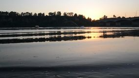 Sunset over the river, boat sails along the river stock video