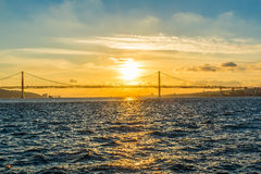 Sunset over the river and the bridge Twenty fifth April. Sunset over the river in Lisbon and the bridge Twenty fifth April stock photo