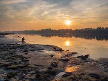 Sunset over a river with a child playint at the coast.  Stock Images