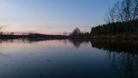 Sunset over the river, clouds are reflected in wa stock video