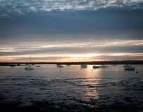 Sunset over river estuary west mersea essex seafront coast boats stock photography