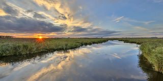 Sunset over river in  marshland nature reserve Stock Photos