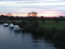 Sunset over the River Ouse, York, England. Sunset over trees and fields and the River Ouse with boats near York, England royalty free stock photo