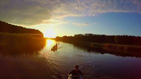 Sunset over river, silhouettes of people in boats, traveling. Stock footage stock video