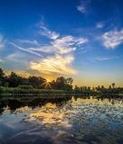 Sunset over the river, summer evening. Light clouds reflected in the water Stock Photo