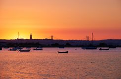 Sunset over the river Tejo, 25th of April Bridge and statue of. Sunset view of the river Tejo, 25th of April Bridge and statue of  Christ the King in Lisbon Stock Photos