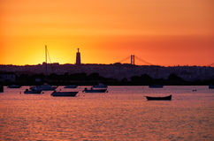 Sunset over the river Tejo, 25th of April Bridge and statue of. Sunset view of the river Tejo, 25th of April Bridge and statue of  Christ the King in Lisbon Royalty Free Stock Image