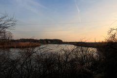 Sunset over the river in the village. Sunset over the river, sunset over the river at the end of winter stock photo