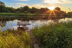 Sunset over the river, wooden bridge. Water lilies, light clouds Stock Photo